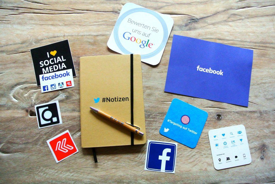 Sobre una mesa se disponen varios elementos, cada uno de ellos identificados como una red social diferente: cuadernos, pegatinas, folios...