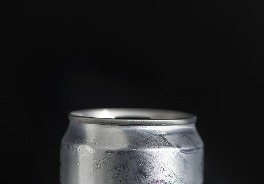 Primer plano de una lata de refresco con fondo negro