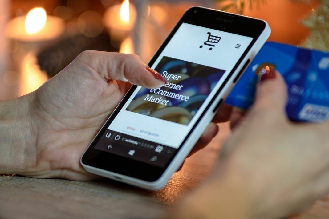 Primer plano de una mano que maneja un smartphone a través de una tienda virtual