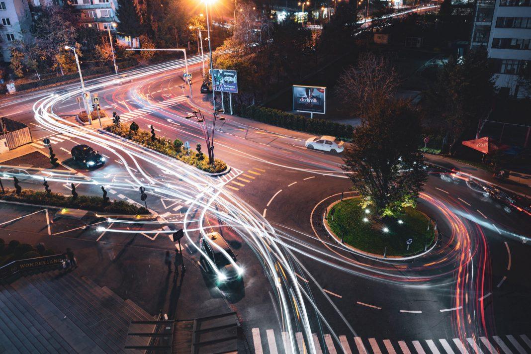 Foto de la calle de una ciudad, vista desde arriba, durante la noche y con tráfico pasando