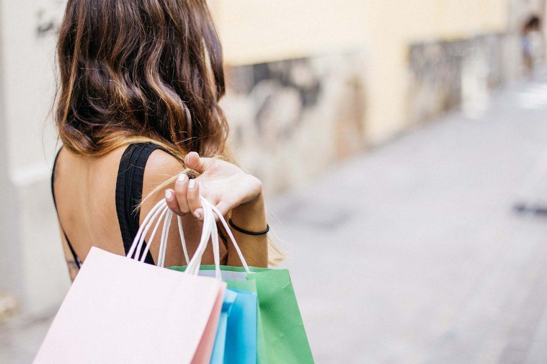 Mujer de espaldas con varias bolsas de compras en la mano