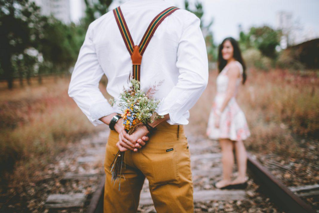 Un hombre esconde un ramo de flores que va a dar a su chica