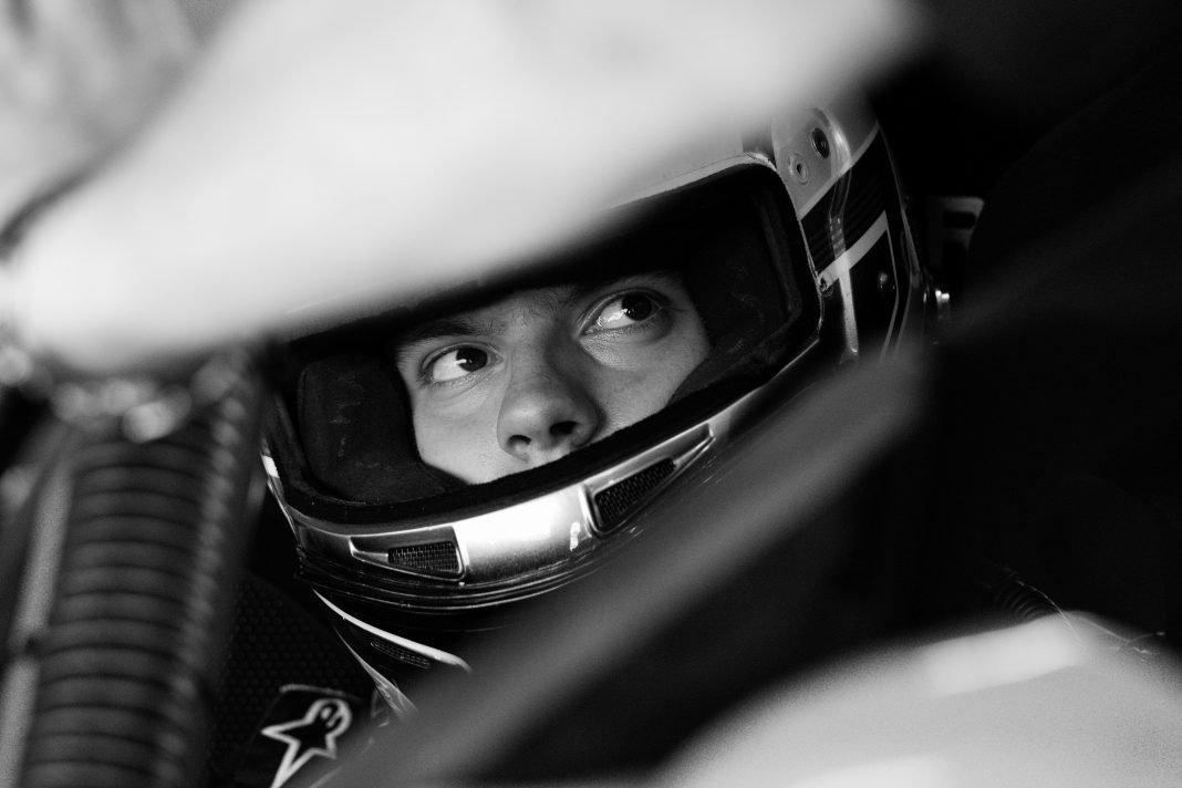 Un piloto de carreras mira con desconfianza a través de la visera de su casco