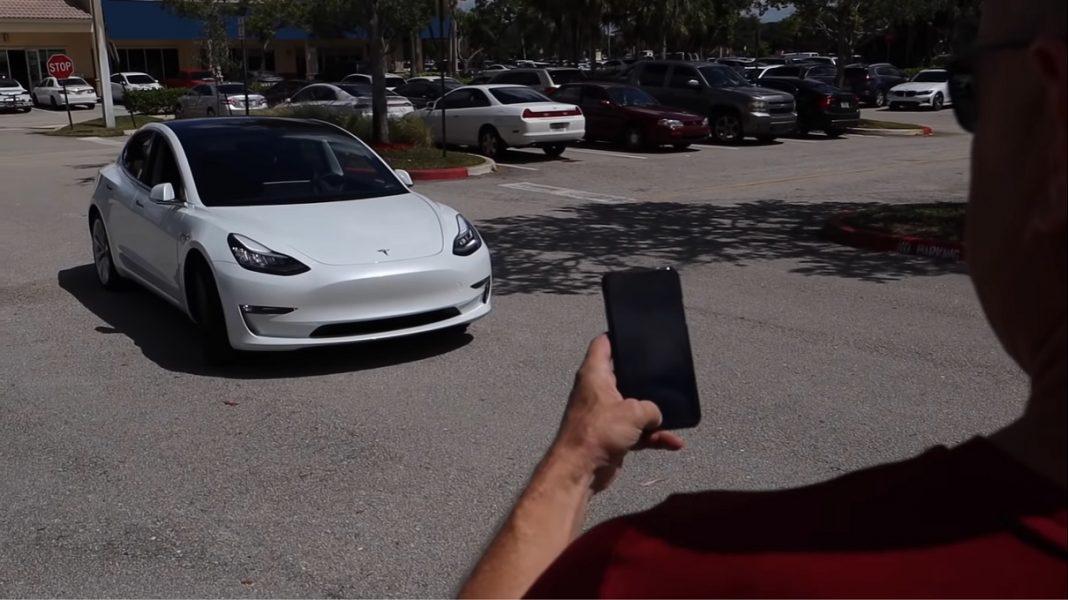 Un hombre controla desde su smartphone a su Tesla Model 3 blanco