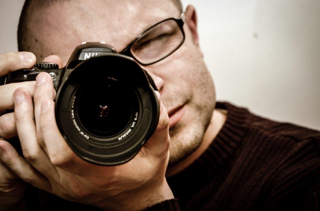 Hombre apunta con su cámara hacia el espectador de la foto