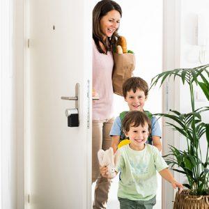 Imagen de una familia entrando por la puerta de su casa.