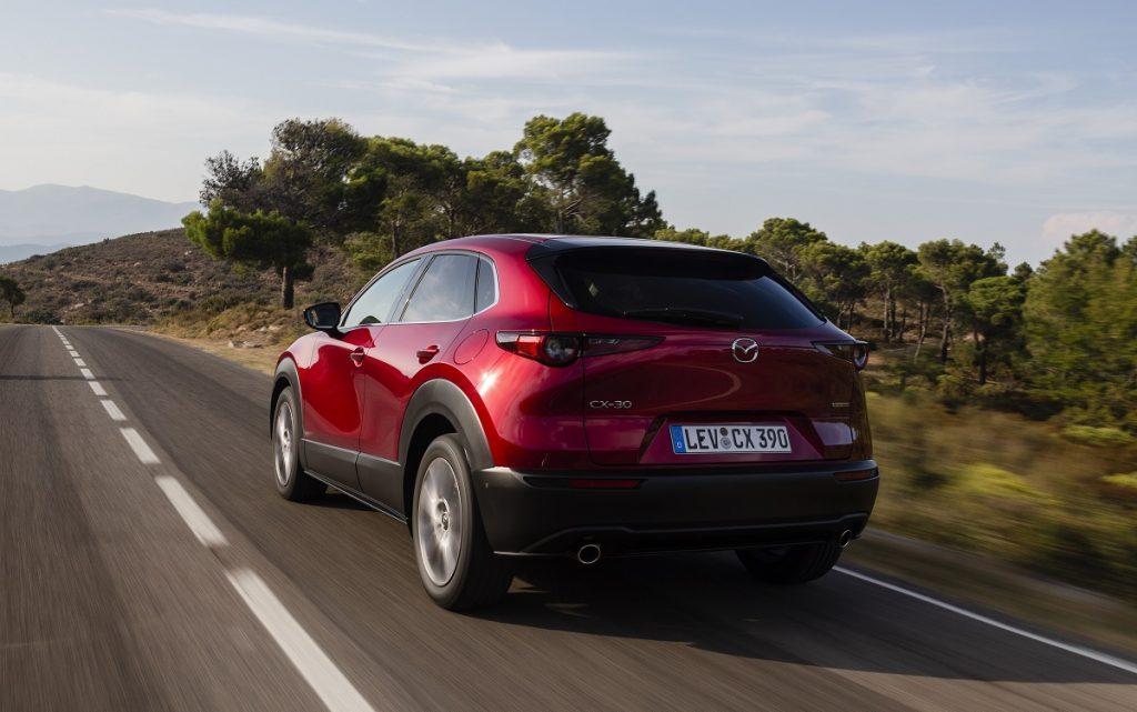 Imagen exterior tres cuartos trasero del nuevo Mazda CX.30 de color rojo en carretera