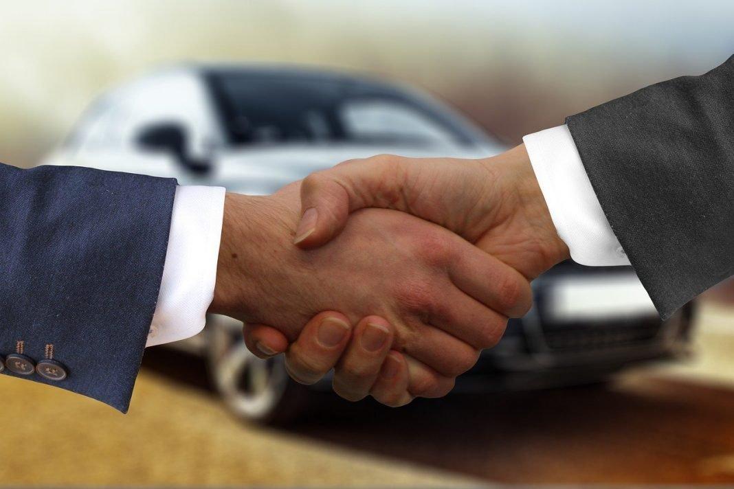 Apretón de manos delante de un coche