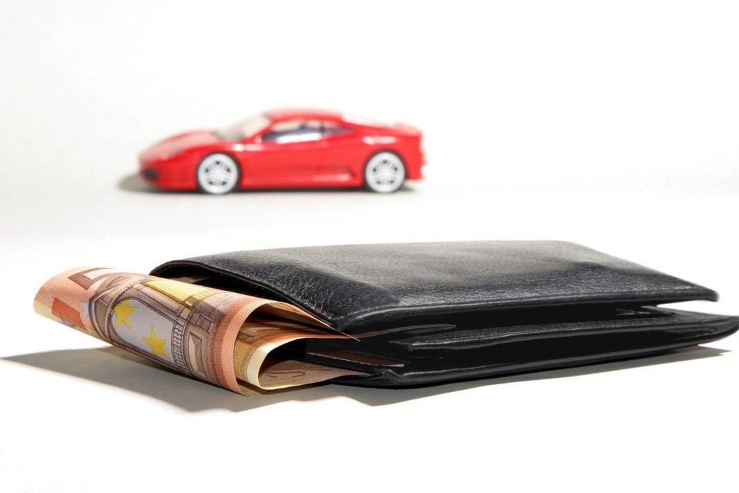 Primer plano de una cartera de la que asoma un fajo de billetes de 50€, con la miniatura de un Ferrari rojo al fondo