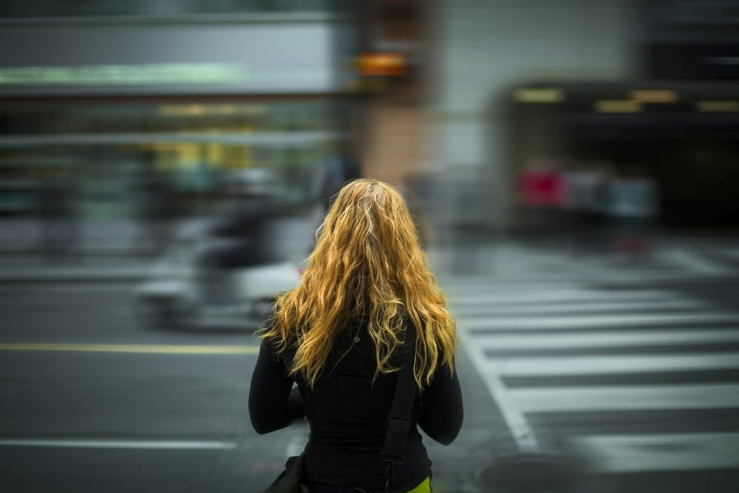 Una niña está en el borde de la acera a punto de cruzar la carretera
