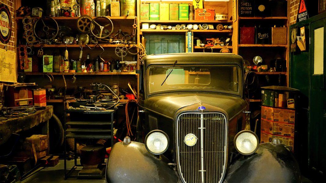 Un viejo taller mecánico con un coche de los años 20 aparcado dentro