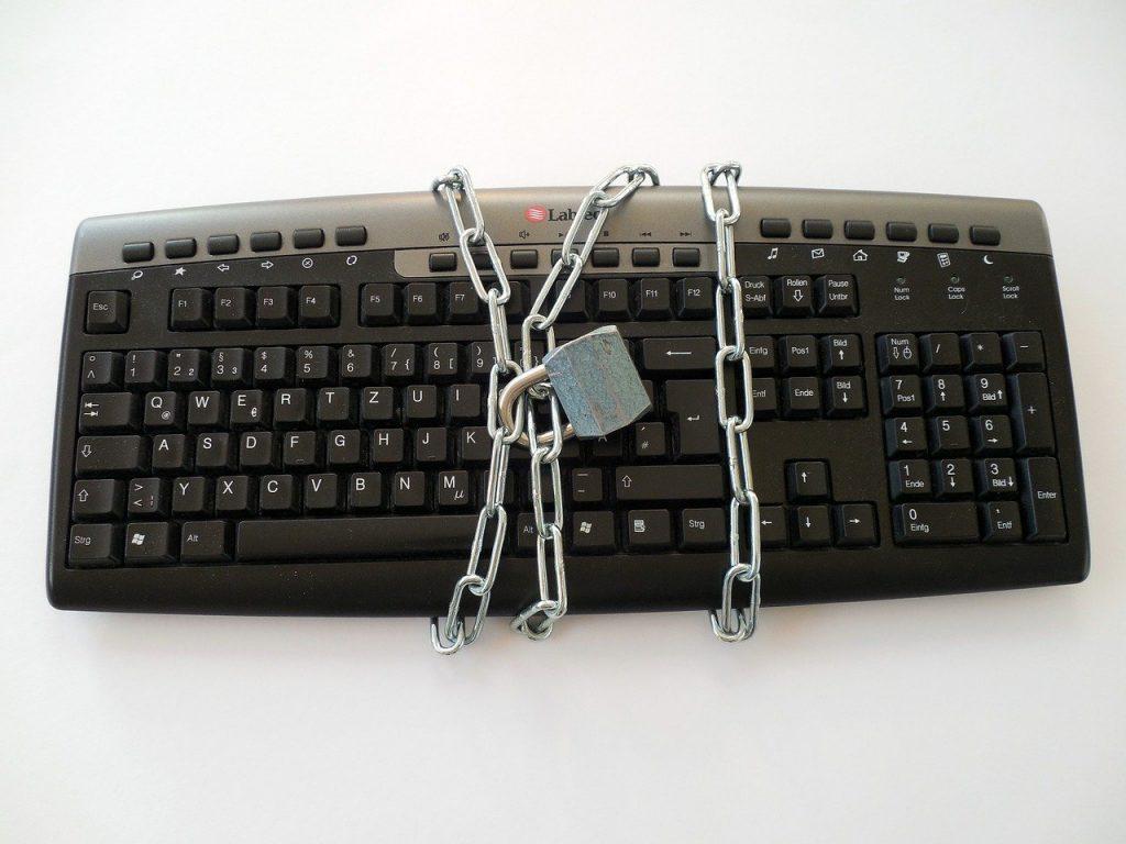 Teclado de ordenador rodeado por una cadena cerrada por un candado