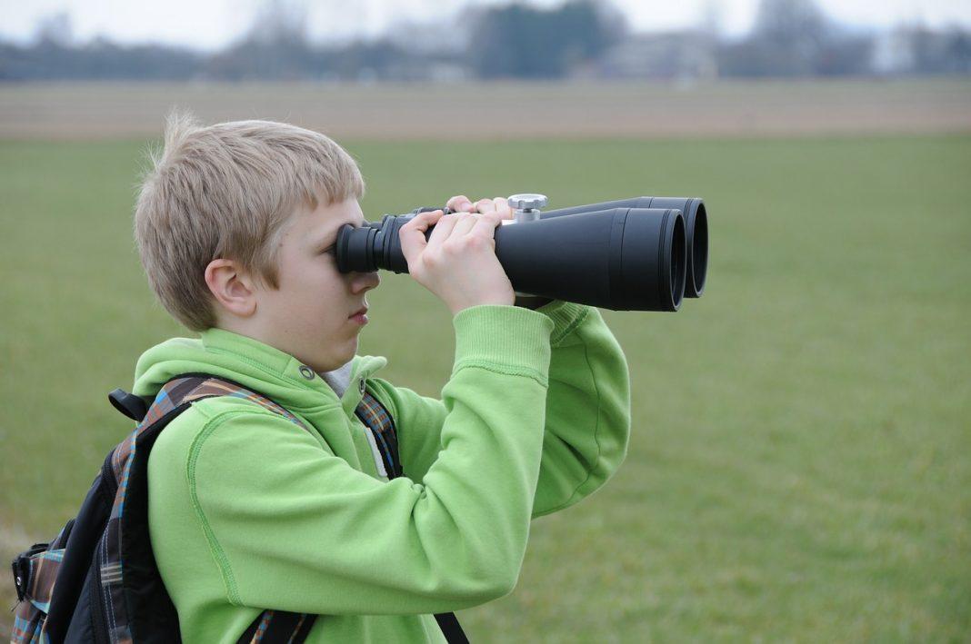 Un niño situado en un parque mira a través de unos prismáticos muy grandes