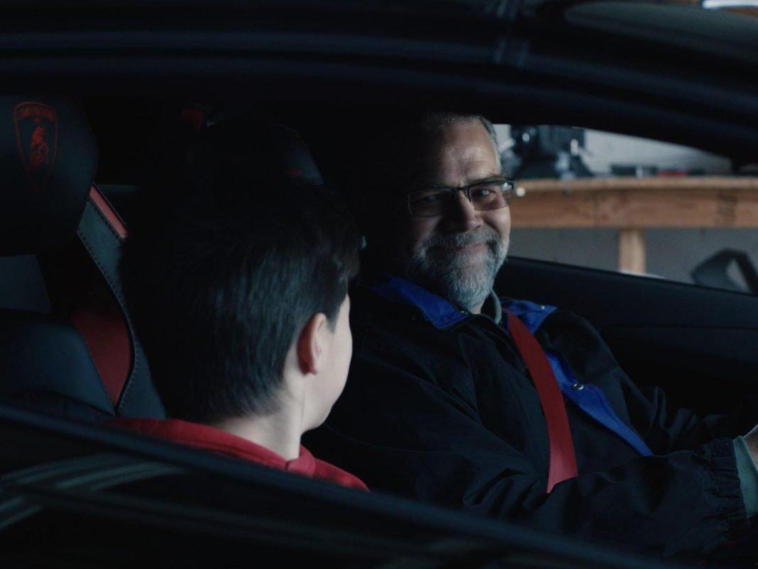Un padre y un hijo sentados dentro de un Lamborghini Aventador