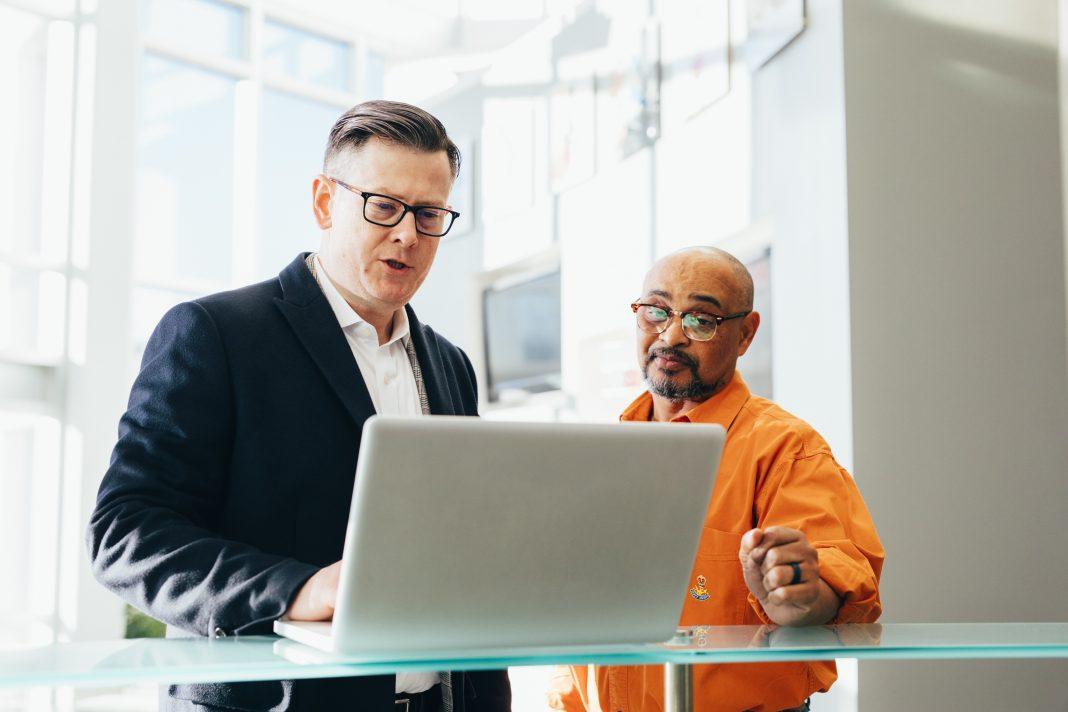 Dos hombres delante de un ordenador con cara de sorpresa