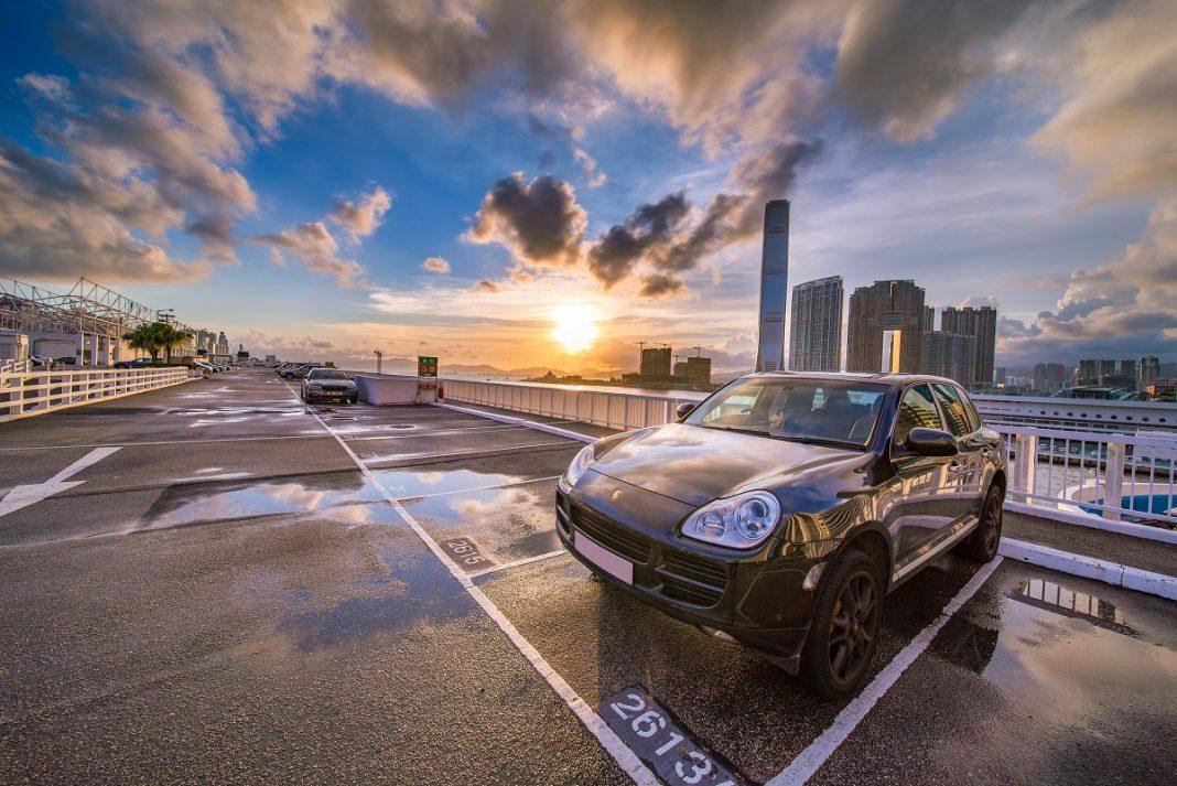 Porsche Cayenne aparcado en un parking exterior con un fondo de ciudad nublada