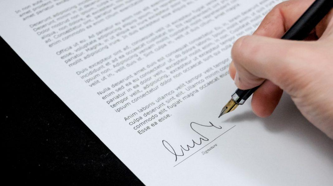 Primer plano de una mano firmando un contrato