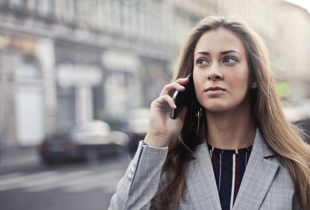 Una chica habla por teléfono en la calle de una ciudad