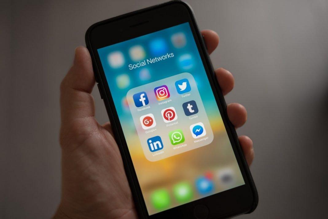 Primer plano de una mano que sujeta un smartphone. En la pantalla se ven los iconos de acceso a redes sociales como Facebook, LinkedIn, Twitter...