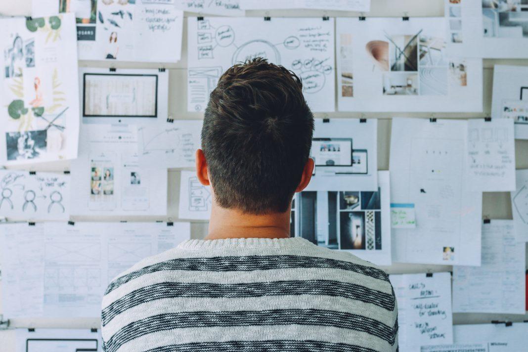 Un hombre mira una pared repleta de folios