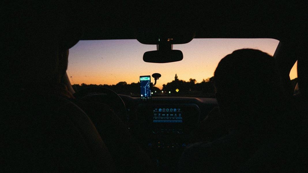 Una pareja maneja su móvil durante la conducción