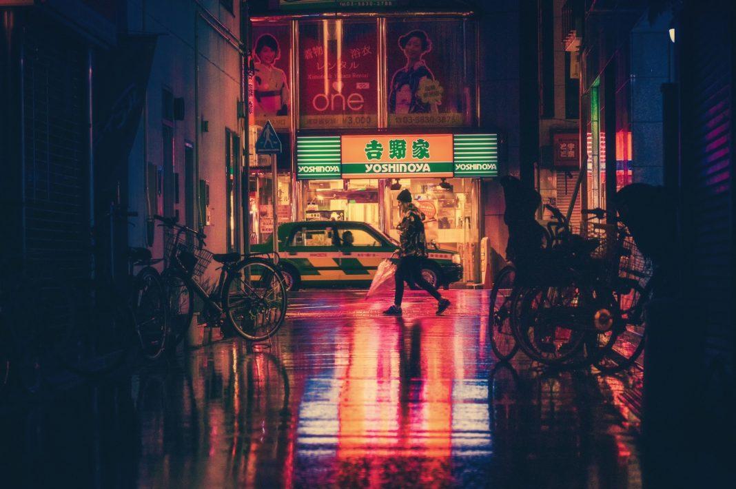 Imagen nocturna de un callejón en una calle de Japón. Se ve un cartel de neón, un coche y una persona andando
