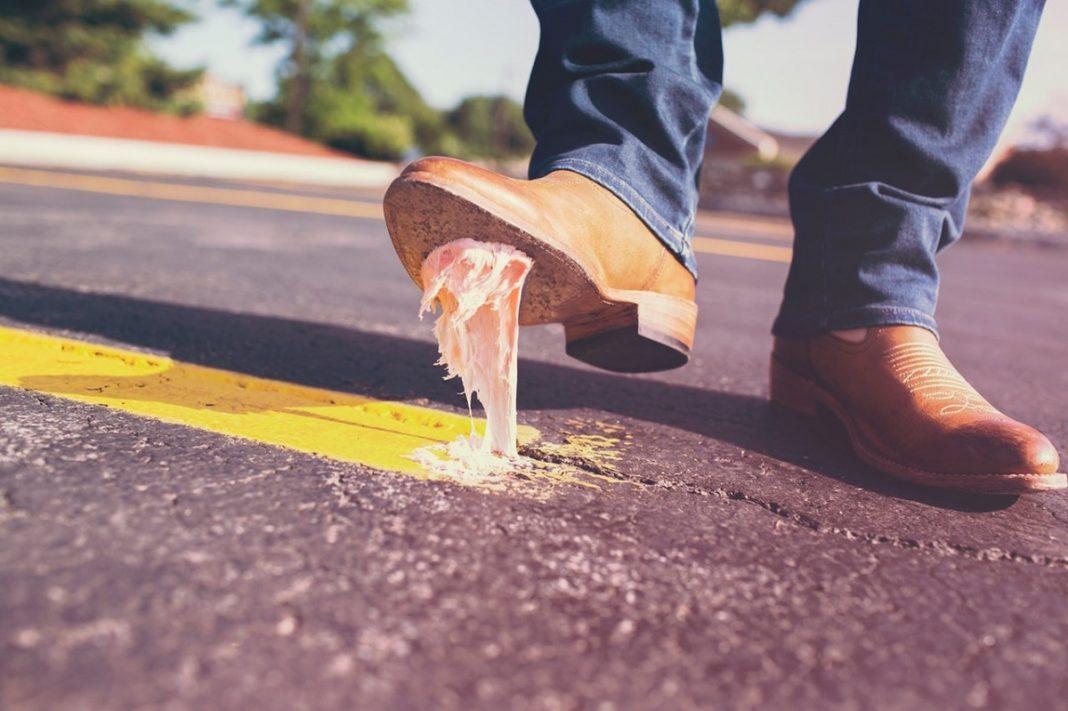 Imagen de la pierna de un hombre que ha pisado un chicle con el zapato