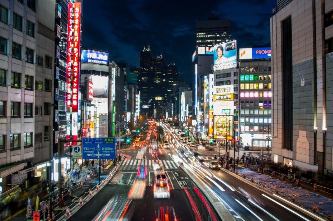 Imagen nocturna de una abarrotada calle de una ciudad japonesa, con carteles de neón y tráfico circulando