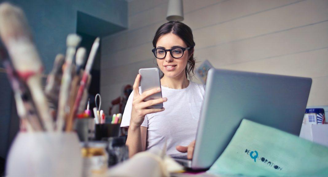 Chica mirando su teléfono móvil sentada en su escritorio