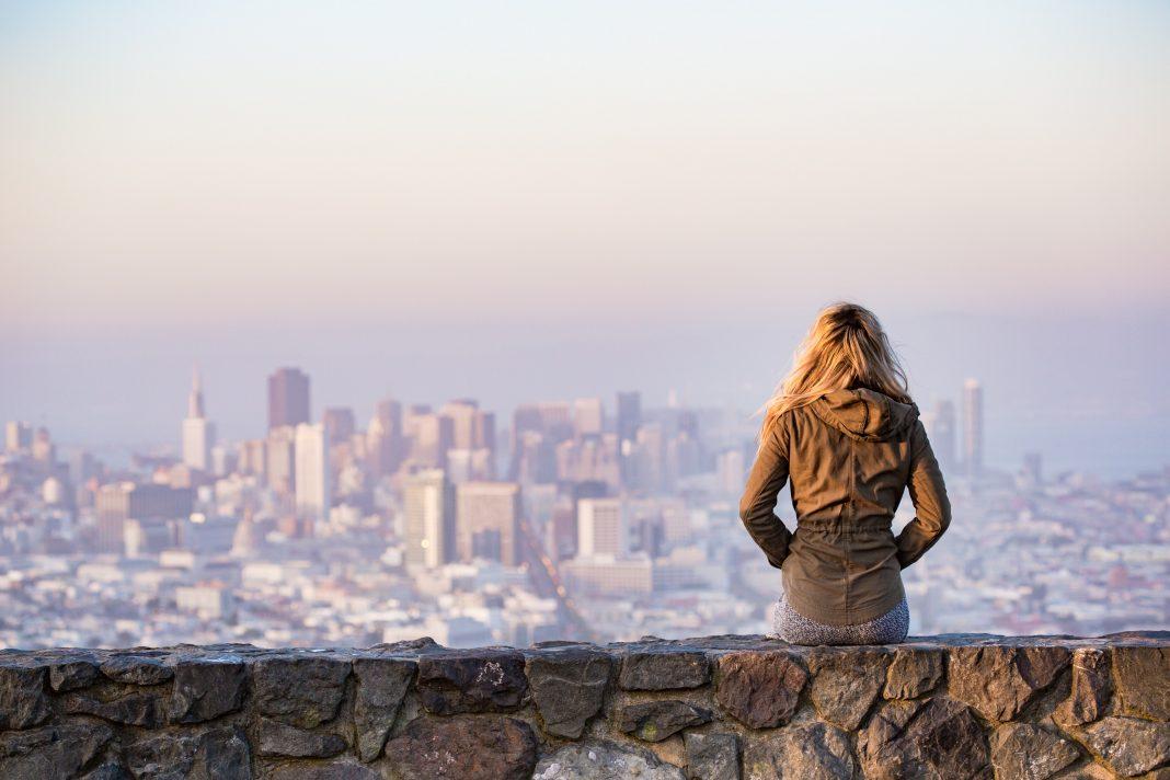 Mujer observa una ciudad desde un mirador lejano
