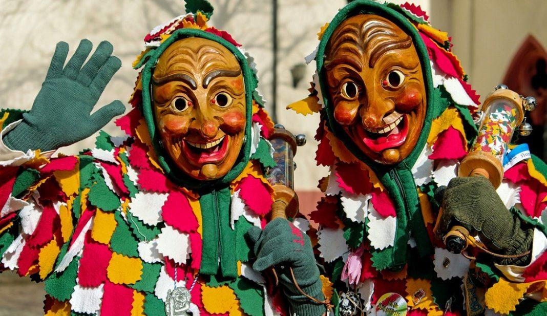 Dos personas disfrazadas con un traje muy raro, de muchos colores y flecos