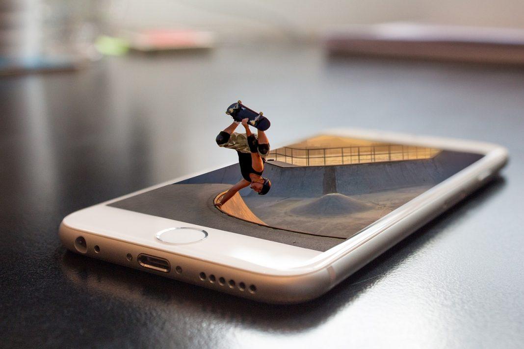 Smartphone sobre una mesa. De la pantalla sale un chico patinando