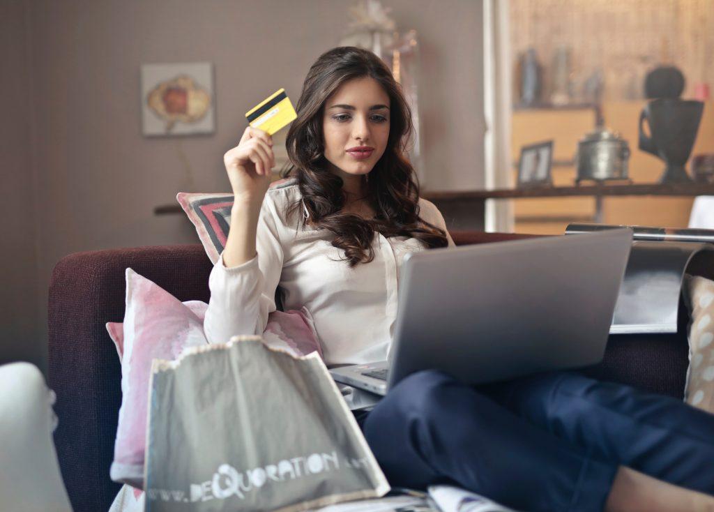 Una mujer está sentada en el sofá de un salón consultando el ordenador con una tarjeta de crédito en la mano y varias bolsas de compra alrededor