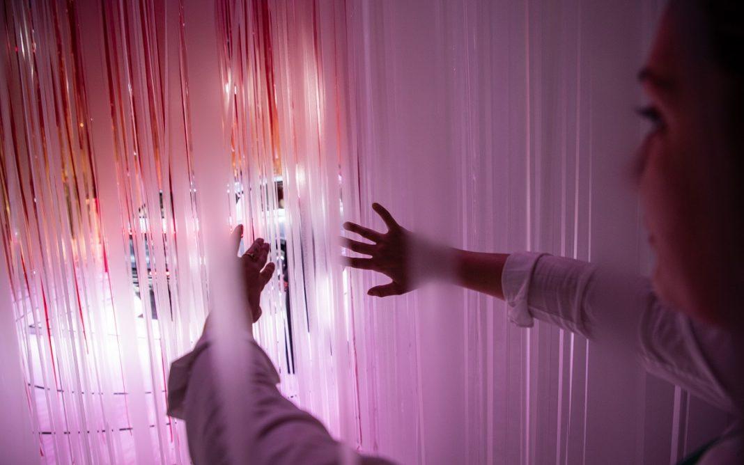 Imagen de una persona mirando un coche futurista tras unas cortinas