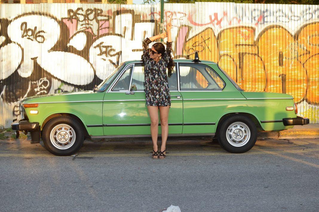 Chica apoyada el capó de un coche