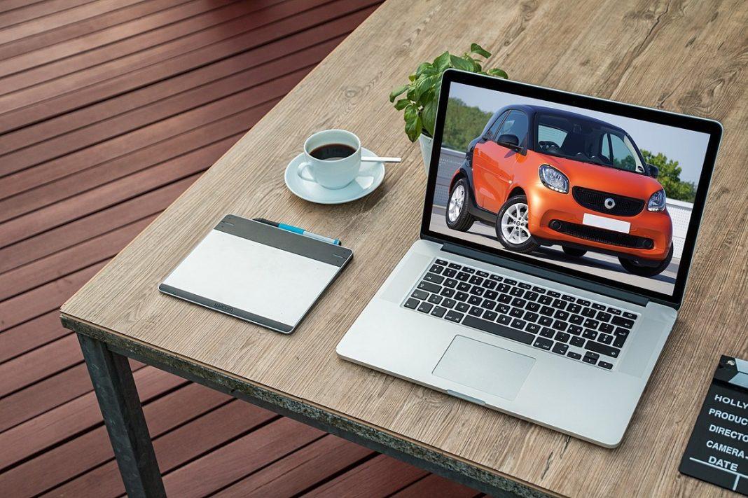 Un ordenador sobre una mesa en un salón. En la pantalla del ordenador está la imagen de un Smart