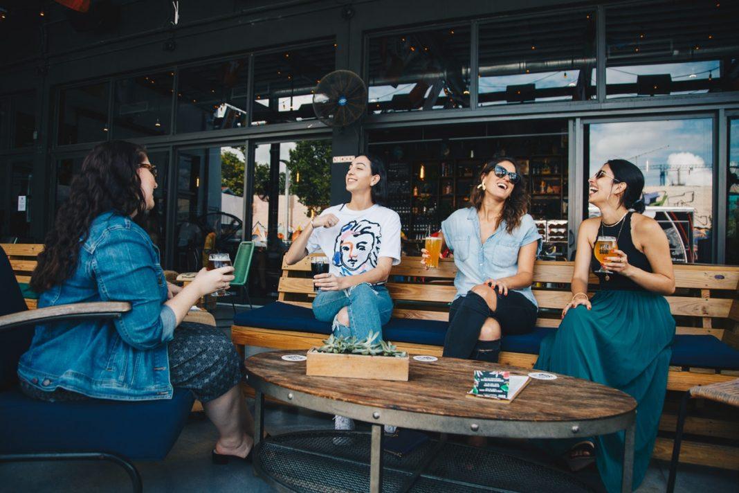 Un grupo de chicas están sentadas en la terraza de un bar tomando algo y charlando alegremente