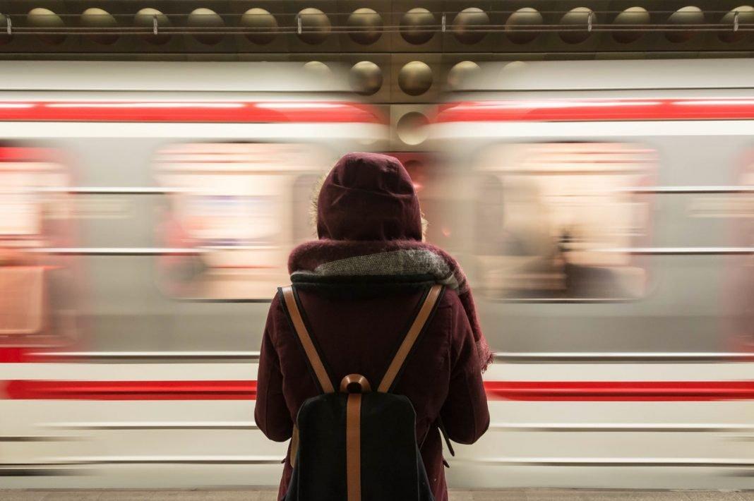Una mujer ve pasar un tren desde el andén de la estación