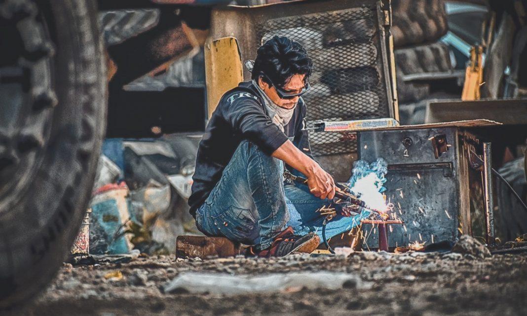 Un hombre está sentado al aire libre en un entorno industrial o de desguace trabajando con un soldador