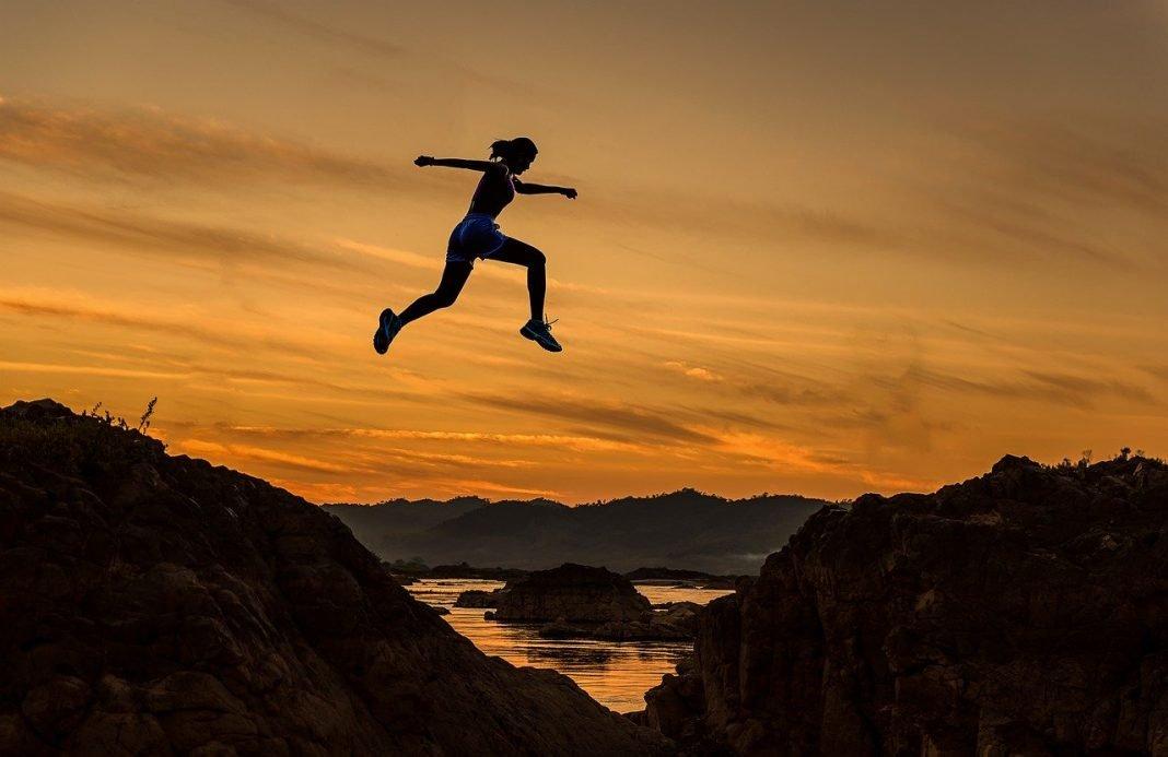 Una persona pega un salto enorme para llegar de una montaña a otra