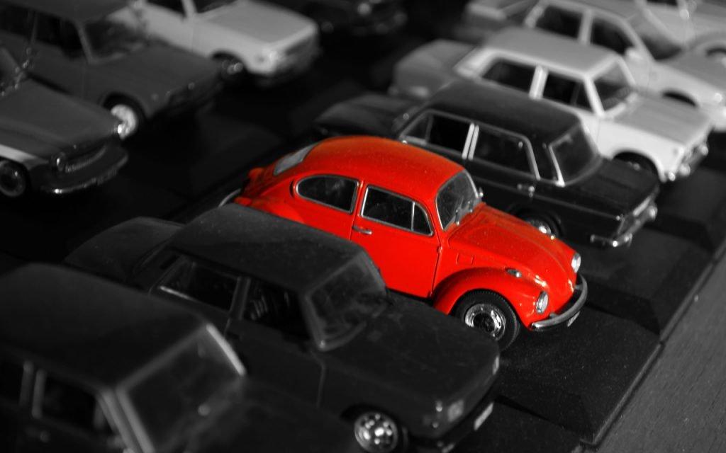Reto hackercar: varios coches en miniatura unos al lado de los otros. Todos son de colores grisáceos salvo un VW Escarabajo rojo