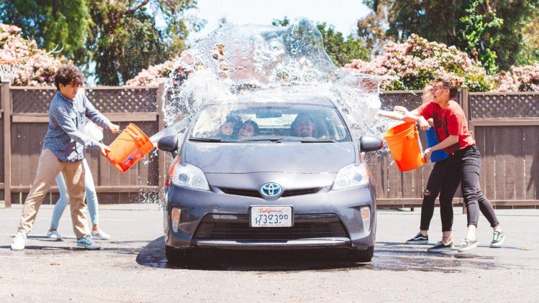 Cuatro niños tiran cubos de agua contra un coche