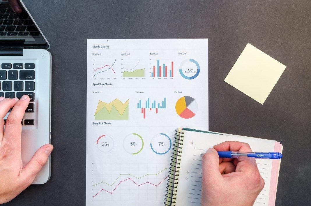 Imagen zenital de una mesa en la que una persona está trabajando con diversos gráficos y papeles