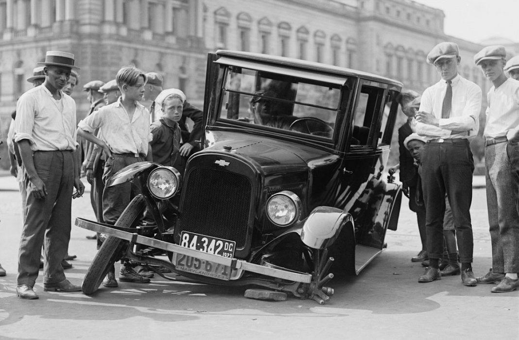 Un coche antiguo con una rueda destrozada
