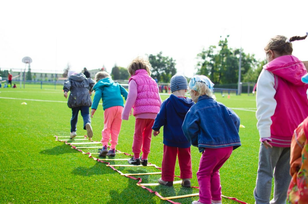 Juego ciberseguridad: unos niños pequeños juegan sobre el césped