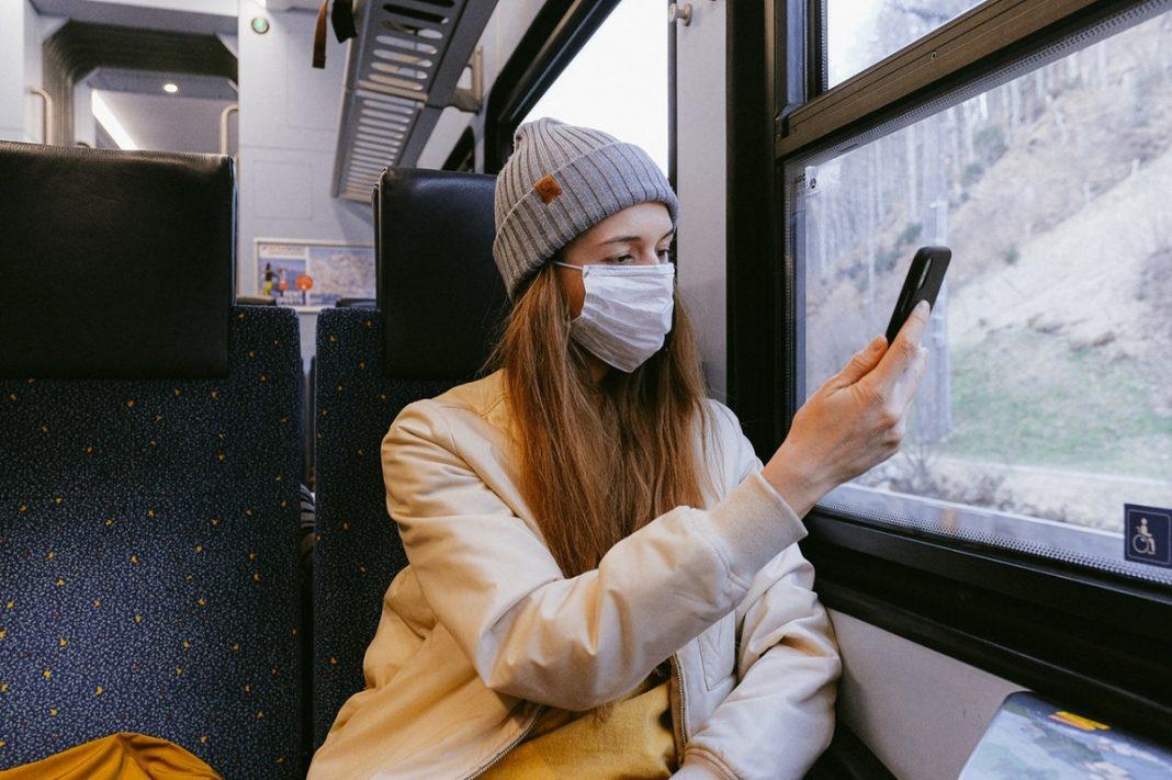 Noticias coronavirus: una mujer va en transporte público con una mascarilla