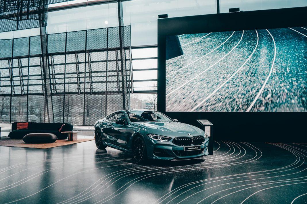 Un BMW está aparcado dentro de un salón de diseño moderno