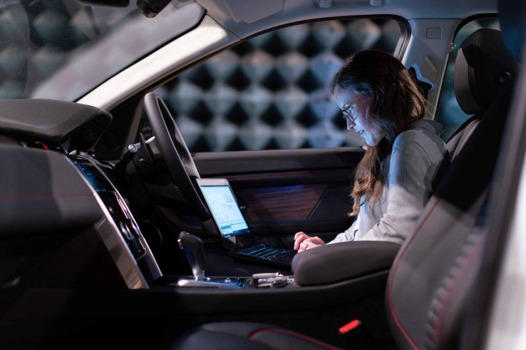 Una mujer está sentada en el asiento del copiloto de un coche conectado con un ordenador sobre las piernas