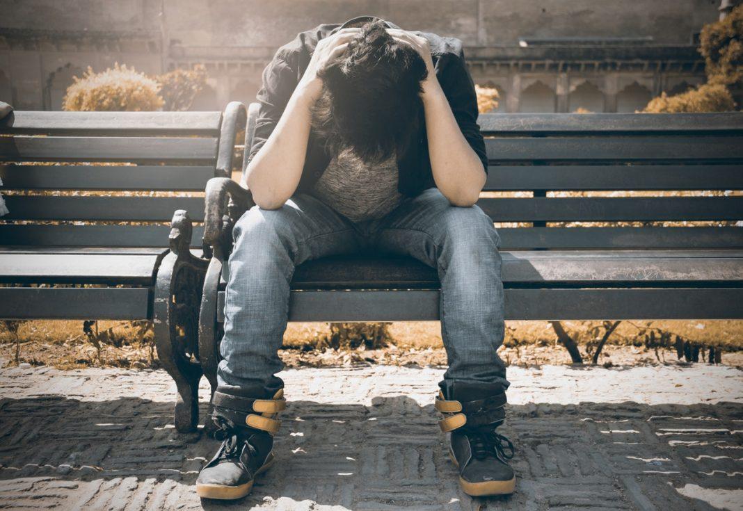 Crisis de imagen: un hombre está sentado en un banco llevándose las manos a la cabeza