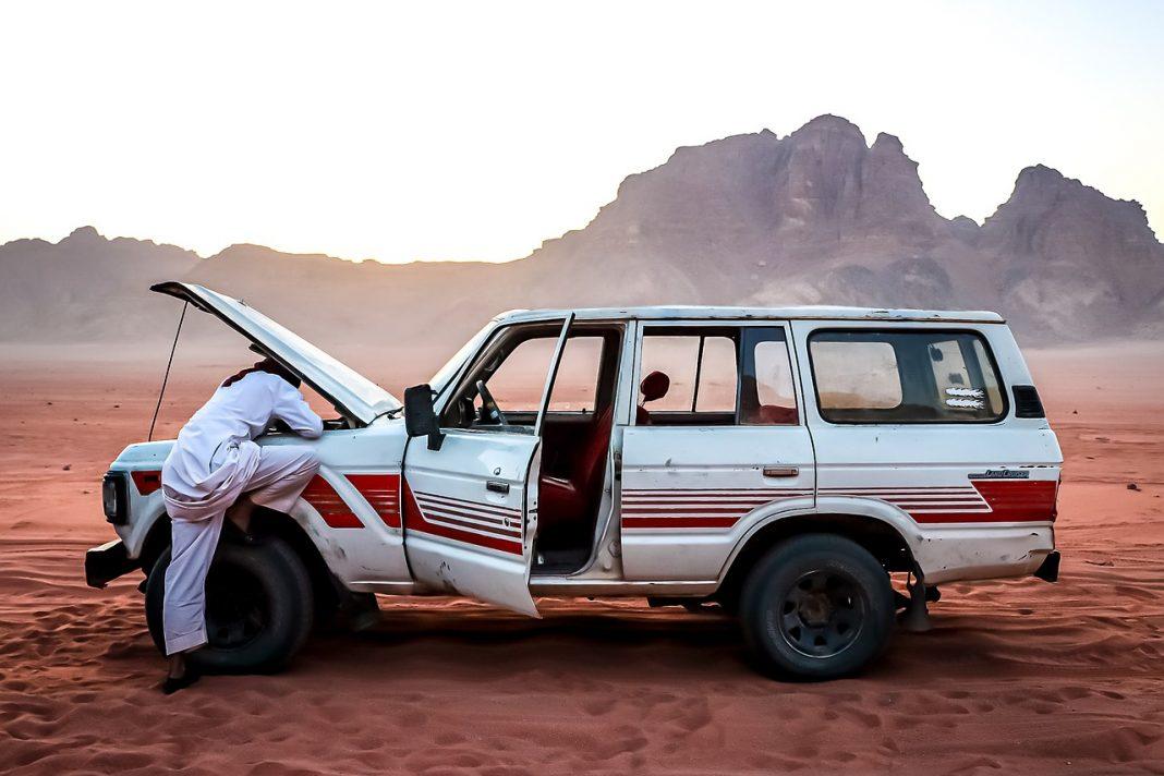 HOmbre mira bajo el capó de un todoterreno en mitad del desierto